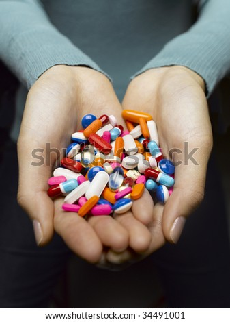 Woman holding pile of pills in cupped hands, close-up - stock photo
