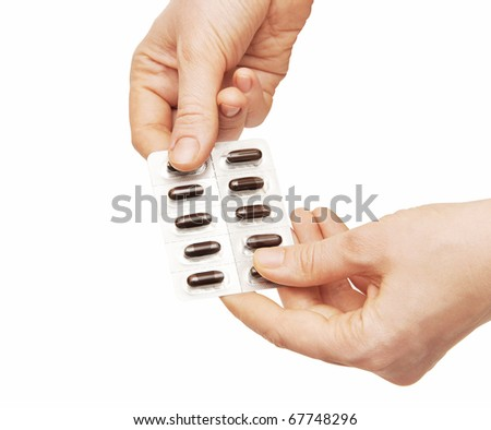 Woman holding pills. Isolated on a white background.