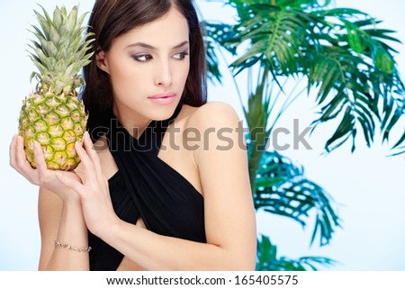 Woman holding pineapple in front of a palm tree