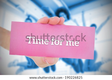 Woman holding pink card saying time for me against fitness class in gym - stock photo