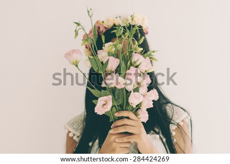 Woman holding pink flowers and hiding behind it - stock photo