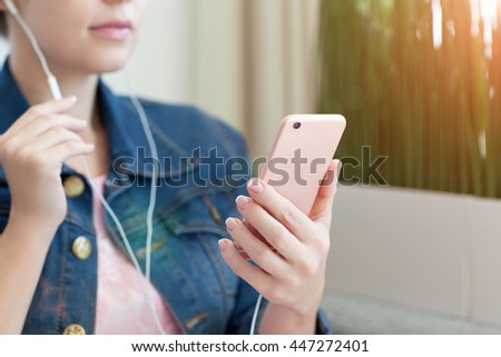 woman holding pink phone and listening to music on headphones