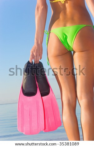 woman holding pink snorkel fins in tropical green bikini on vacation