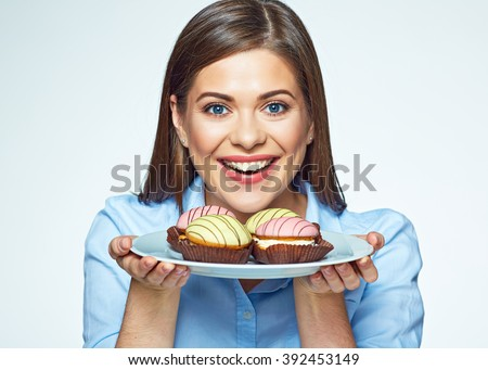 Woman holding plate with cookies and she wants to eat them. Happy girl with macaron french cookies.