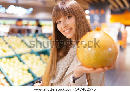 Woman holding pomelo at supermarket - stock photo