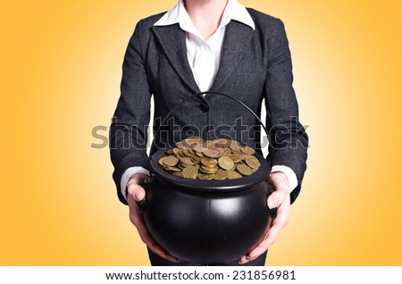 Woman holding pot of gold coins - stock photo