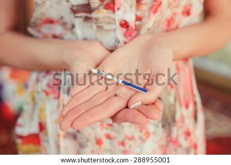 Woman holding pregnancy test. - stock photo