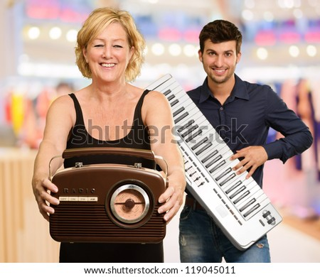 Woman Holding Radio In front Of Man Holding Piano, Indoors - stock photo