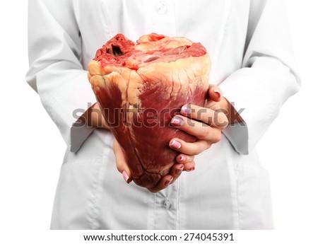 Woman holding raw animal heart close up - stock photo