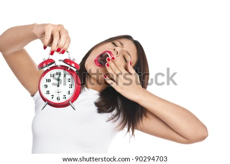 Woman holding red alarm clock yawning isolated on white. Focus is on clock. - stock photo