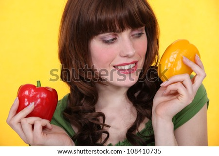 Woman holding red and yellow peppers