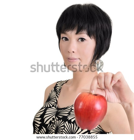 Woman holding red apple and looking at you, half length closeup portrait on white background.