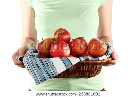Woman holding red apples in wicker basket with napkin on white background - stock photo