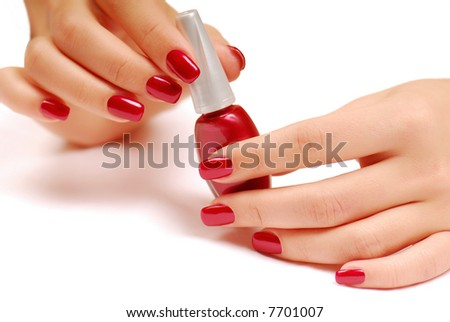 Woman holding red bottle of nail polish  in her arms.