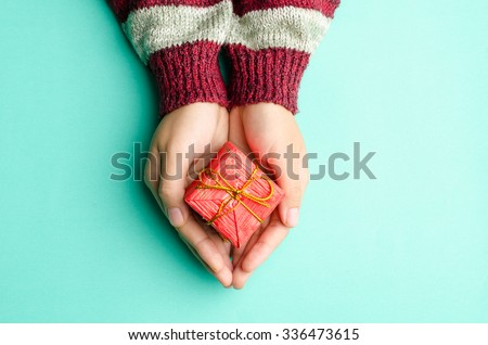 Woman holding red giftbox by hand on green background - stock photo