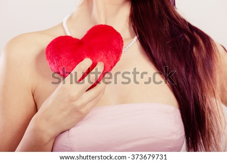 Woman holding red heart love symbol studio in hand closeup. Valentines day happiness concept