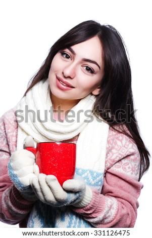 Woman holding red mug wearing pullover, scarf and gloves