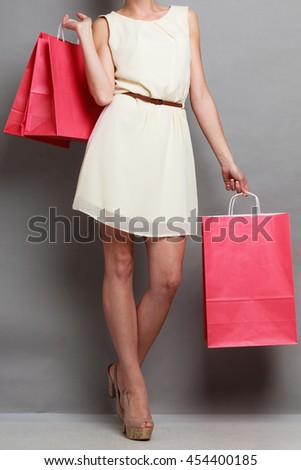 Woman holding red paper shopping bags. Elegant lady bright dress buying clothes. Sale and retail.