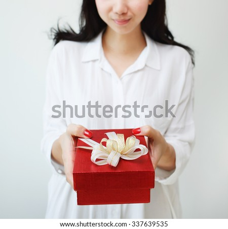 Woman holding red present box with ribbon - stock photo