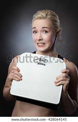 woman holding scales looking worried with the words bad news written on the scales - stock photo