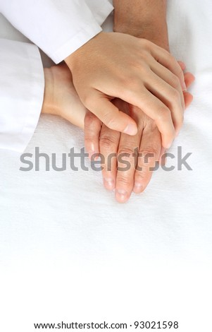 Woman holding senior woman's hand on bed