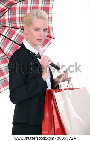 Woman holding shopping backs and umbrella - stock photo