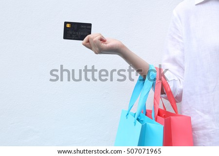 Woman holding shopping bag and credit card on white background