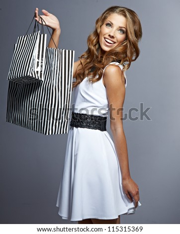 Woman holding shopping bags against a grey background - stock photo