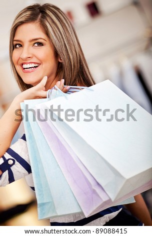 Woman holding shopping bags and looking happy