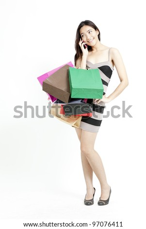 Woman holding shopping bags and talking on mobile phone against a white background - stock photo