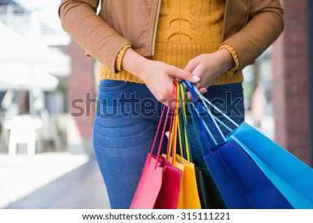 Woman holding shopping bags at a boutique - stock photo