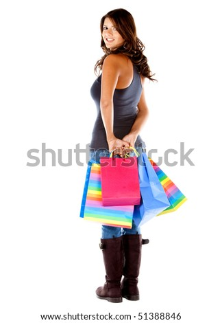 Woman holding shopping bags looking back isolated over a white background