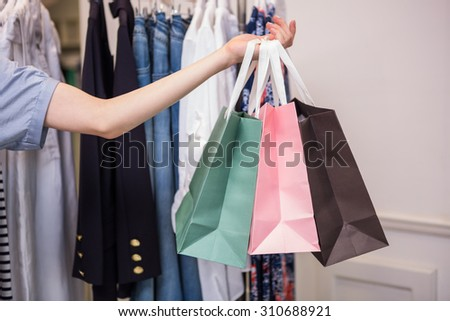 Woman holding shopping bags out in fashion boutique