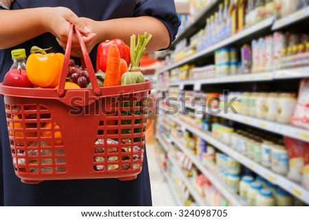 woman holding shopping basket in grocery store - stock photo