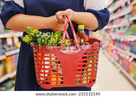 woman holding shopping basket in supermarket - stock photo