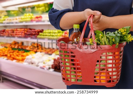 woman holding shopping basket in supermarket,fruit zone background - stock photo