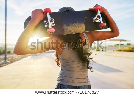 woman holding skate board behind her back looking at sunset shot with lens flare