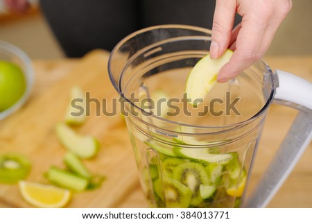 Woman holding sliced green apple over blender.