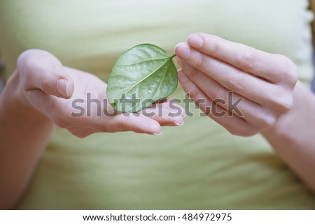 Woman holding small green leaf