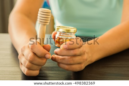 Woman holding small jar of honey with small honey dipper.