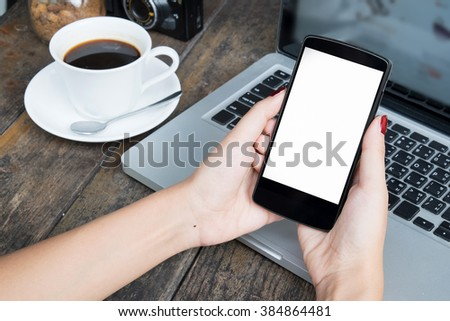 woman holding smart phone and with laptop at office in morning light.vintage effect - stock photo