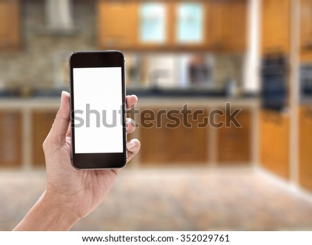 Woman holding smart phone or mobile phone with blank mobile.over blurred kitchen background for working online on vacation. - stock photo