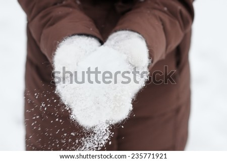 Woman holding snow in her hands  - stock photo
