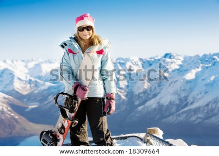 Woman holding snowboard with mountains in background - stock photo