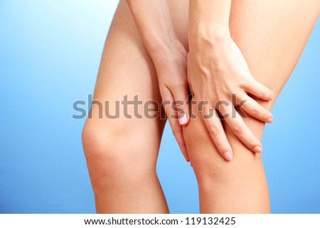 woman holding sore knee, on blue background - stock photo