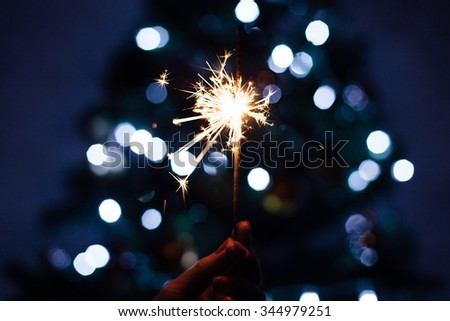 Woman holding sparkler with Christmas tree glitter in background - stock photo