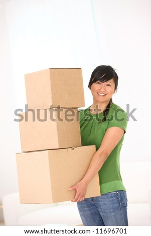 Woman holding stack of cardboard boxes