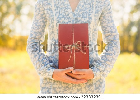 woman holding stacked books with ribbon - stock photo