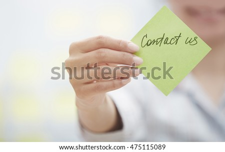 Woman holding sticky note with Contact us text