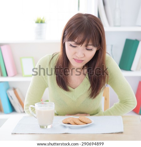 Woman holding stomach and suffering stomachache, while having dairy milk and cookies as breakfast, sitting at dining table.Young people indoors living lifestyle at home.   - stock photo